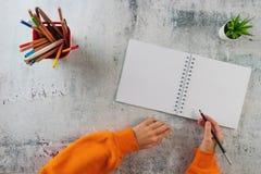 Il bambino scrive a matita in un taccuino immagini stock