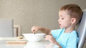 Il bambino si siede al tavolo da cucina e mangia la minestra Il concetto di alimenti per bambini sani stock footage