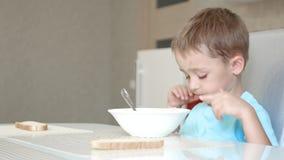 Il bambino si siede al tavolo da cucina e mangia la minestra Il concetto di alimenti per bambini sani Movimento del cursore della stock footage
