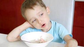Il bambino si siede al tavolo da cucina e mangia la minestra della salsiccia Il concetto di alimenti per bambini sani video d archivio