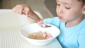 Il bambino si siede al tavolo da cucina e mangia il primo piano della minestra Il concetto di alimenti per bambini sani stock footage