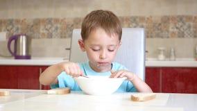 Il bambino si siede al tavolo da cucina, mangia il pane e la minestra video d archivio