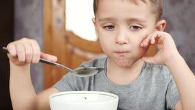 Il bambino si siede al tavolo da cucina, mangia il pane e la minestra Il concetto di alimenti per bambini sani stock footage