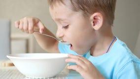 Il bambino si siede al tavolo da cucina, mangiante la minestra con un cucchiaio da un piatto bianco video d archivio