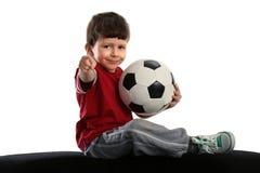 Il bambino si siede con la sfera di calcio Fotografie Stock Libere da Diritti