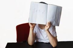 il bambino si siede e fa il compito su un fondo bianco fotografia stock libera da diritti