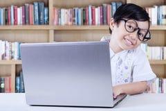 Il bambino si siede nella biblioteca con il computer portatile Immagine Stock Libera da Diritti