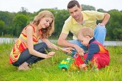 Il bambino si siede su erba con i genitori e su giochi con a Fotografia Stock