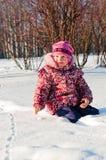 Il bambino si siede su neve ed osserva Immagine Stock
