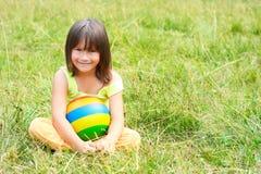 Il bambino si siede su un'erba Fotografia Stock Libera da Diritti