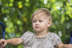 Il bambino si siede su una collina Fotografia Stock Libera da Diritti