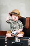 Il bambino si siede su una valigia e con una macchina fotografica in sue mani Immagine Stock