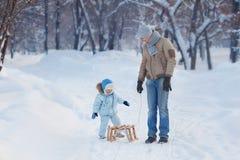 Il bambino si siede sulla slitta, le sue attese del padre Fotografie Stock Libere da Diritti