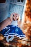 Il bambino si siede sulle scale di vecchia casa fotografia stock