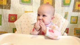 Il bambino si siede in una sedia per il cibo e tiene un cucchiaio in sua mano video d archivio