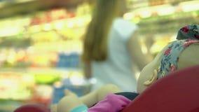Il bambino si siede in una sedia specialmente fornita nel supermercato stock footage