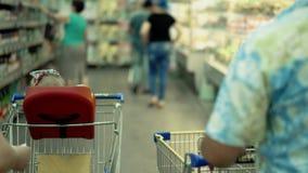 Il bambino si siede in una sedia specialmente fornita nel supermercato video d archivio
