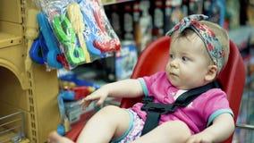 Il bambino si siede in una sedia specialmente fornita nel supermercato archivi video