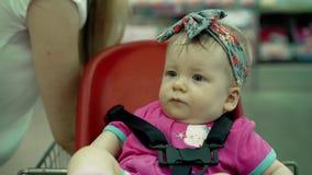 Il bambino si siede in una sedia specialmente fornita in un carrello stock footage