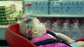 Il bambino si siede in una sedia specialmente fornita stock footage