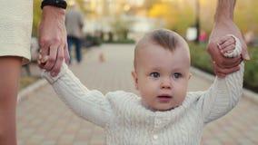 Il bambino si tiene per mano dei genitori video d archivio