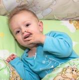 Il bambino si trova in letto e dita di spinta in una bocca Fotografia Stock Libera da Diritti