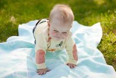 Il bambino si trova su un copriletto Fotografia Stock