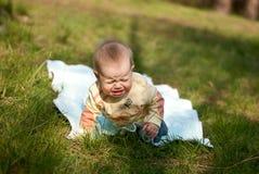 Il bambino si trova su un copriletto Immagine Stock