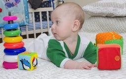 Il bambino si trova sul letto con i giocattoli e lo sguardo a sinistra Immagini Stock Libere da Diritti