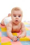 Il bambino si trova sulla stuoia lavorata a maglia Fotografie Stock Libere da Diritti