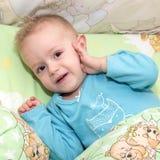 Il bambino si trova in un letto e sta andando cadere addormentato, sollevando la maniglia ad un orecchio Immagine Stock Libera da Diritti