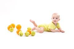 Il bambino sorpreso sveglio esamina la mela verde su un fondo bianco fotografia stock