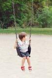 Il bambino sorridente felice del ragazzino in maglietta e jeans mette su oscillazione sul campo da giuoco del cortile fuori Immagini Stock