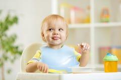 Il bambino sorridente scherza il ragazzo che si mangia con il cucchiaio Fotografia Stock