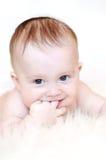 Il bambino sorridente tiene il dito in bocca Fotografie Stock Libere da Diritti