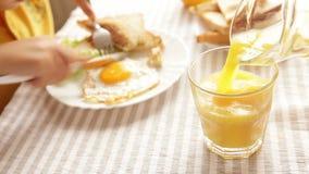 Il bambino sta avendo sua prima colazione - uova fritte, pane tostato, succo - prima di andare a scuola archivi video