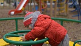 il bambino sta filando su un'oscillazione nel campo da giuoco nel parco stock footage