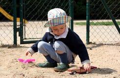 Il bambino sta giocando con i giocattoli su un campo da giuoco Immagini Stock Libere da Diritti