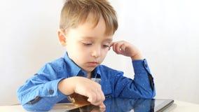 Il bambino sta giocando con la compressa, c'è una tazza di tè sulla tavola Internet e tecnologie wireless E archivi video