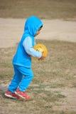 Il bambino sta giocando con una palla gialla Fotografie Stock