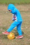 Il bambino sta giocando con una palla gialla Fotografia Stock