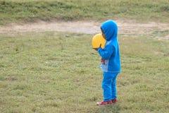 Il bambino sta giocando con una palla gialla Immagini Stock Libere da Diritti