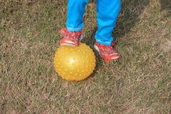 Il bambino sta giocando con una palla gialla Immagine Stock Libera da Diritti