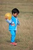 Il bambino sta giocando con una palla gialla Fotografia Stock Libera da Diritti