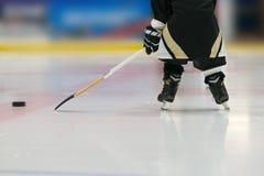 Il bambino sta giocando l'hockey con il bastone ed il disco La foto è stata presa dalla parte posteriore: i pattini ed il bastone Fotografia Stock Libera da Diritti