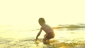 Il bambino sta giocando sulla spiaggia del mare ed è caduto nell'acqua, contro lo sfondo di un declino ad un passo rallentato archivi video