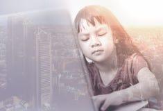 Il bambino sta lavorando il computer portatile di persona dura con la doppia esposizione sulla città immagini stock