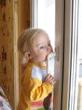 Il bambino sta levandosi in piedi alla finestra Immagine Stock Libera da Diritti