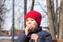 Il bambino sta mangiando la dolcezza nel campo da giuoco Ritratto emozionale del primo piano immagine stock