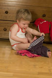Il bambino sta mettendo sui pantaloni Immagine Stock
